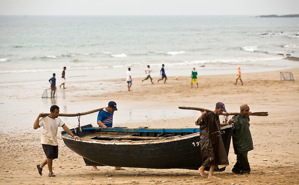 Fishermen carry their fishing boats up the long beach using tradtional methods in Taghazout, Morocco.Taghazout is a popular surfing town north of Agadir.