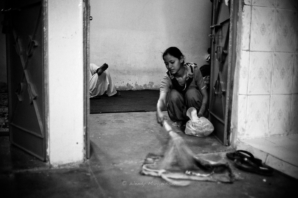 A young woman sweeps up the floor while her male family member rests in the other room. <br /> Pakistan is still a conservative and male orientated society where women still aren't regarded as equal. Karachi, Pakistan, 2010