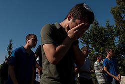 People pray at a joint funeral for the three Israeli teens at a cemetery in Modi'in near Jerusalem, on July 1, 2014. The three Israeli teens whose bodies were found Monday evening were brought to rest side by side on Tuesday at a joint funeral held in Modi'in near Jerusalem. Tens of thousands of people participated in the funeral, including Prime Minister Benjamin Netanyahu and President Shimon Peres, who eulogized the three, whose caskets were wrapped with Israeli flags. EXPA Pictures © 2014, PhotoCredit: EXPA/ Photoshot/ Li Rui<br /> <br /> *****ATTENTION - for AUT, SLO, CRO, SRB, BIH, MAZ only*****