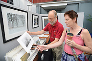 NEW HOPE, PA - SEPTEMBER 06: Photographer Donald Schoenleber (L) of Doylestown, Pennsylvania shows some of his work to Sally Kocher Miller of Maple Glenn, Pennsylvania during Bucks County Guild of Craftsmen's third annual Fine Crafts show at the New Hope Winery September 6, 2014 in New Hope, Pennsylvania. (Photo by William Thomas Cain/Cain Images)