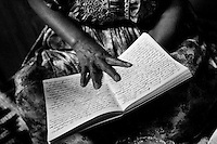 Estella Chuvac shows her diary about her past, while sitting on her bed at Nuevos Horizantes, in Quetzaltenango, Guatemala, on Saturday, May 12, 2007. Words fit tightly on every line of every page describing her life of years of physical abuse by her husband.