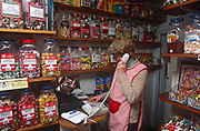 A nineties sweet shop keeper makes a phone call and works out a price using a store calculator, in a shop called The Sugar Boy, on 18th May 2000, in Canterbury, Kent, England.