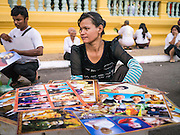 """31 JANUARY 2013 - PHNOM PENH, CAMBODIA: A woman sells photos and portraits of Cambodian King Norodom Sihanouk in front of the Royal Palace in Phnom Penh. Norodom Sihanouk (31 October 1922- 15 October 2012) was the King of Cambodia from 1941 to 1955 and again from 1993 to 2004. He was the effective ruler of Cambodia from 1953 to 1970. After his second abdication in 2004, he was given the honorific of """"The King-Father of Cambodia."""" Sihanouk served two terms as king, two as sovereign prince, one as president, two as prime minister, as well as numerous positions as leader of various governments-in-exile. He served as puppet head of state for the Khmer Rouge government in 1975-1976. Most of these positions were only honorific, including the last position as constitutional king of Cambodia. Sihanouk's actual period of effective rule over Cambodia was from 9 November 1953, when Cambodia gained its independence from France, until 18 March 1970, when General Lon Nol and the National Assembly deposed him. Upon his final abdication, the Cambodian throne council appointed Norodom Sihamoni, one of Sihanouk's sons, as the new king. Sihanouk died in Beijing, China, where he was receiving medical care, on Oct. 15, 2012. His funeral procession, which will wind through Phnom Penh is Friday, Feb.1 and his cremation is on Feb. 4, 2013. Over a million people are expected to attend the service.    PHOTO BY JACK KURTZ"""