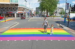 ©Licensed to London News Pictures 16/06/2020<br /> Woolwich, UK. A father and daughter using a colourful crossing in Woolwich town centre, Woolwich. Rainbow pedestrian crossings return to Greenwich Borough to show support for Gay pride month. Crossings in Eltham,Greenwich, plumstead,Charlton and Woolwich have had a rainbow make over bringing some colour to the streets in South East London. Photo credit: Grant Falvey/LNP