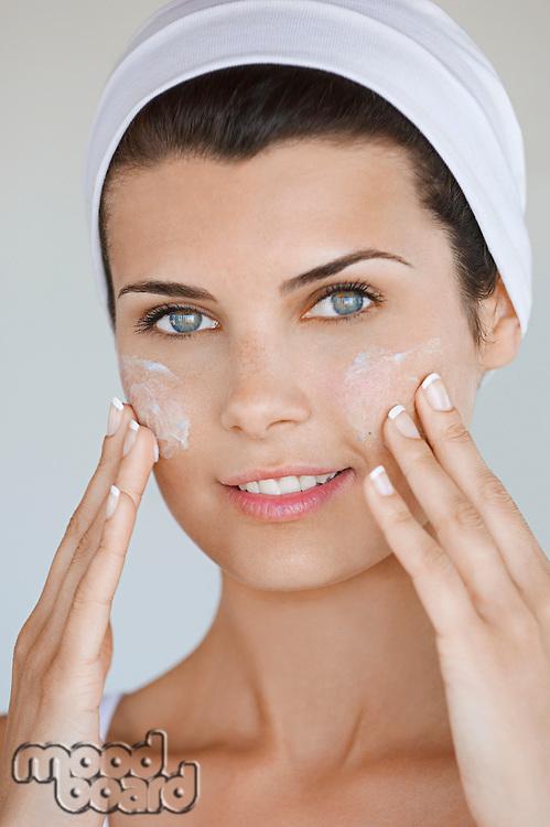 Porrait of young woman applying beauty cream