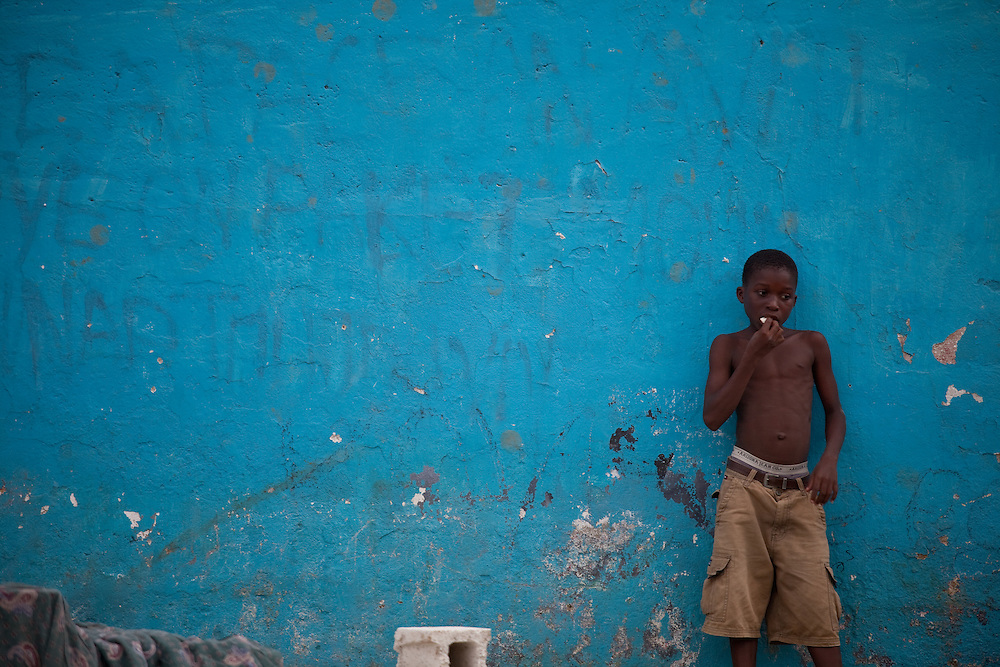 A boy stands against a wall in Port au Prince Haiti