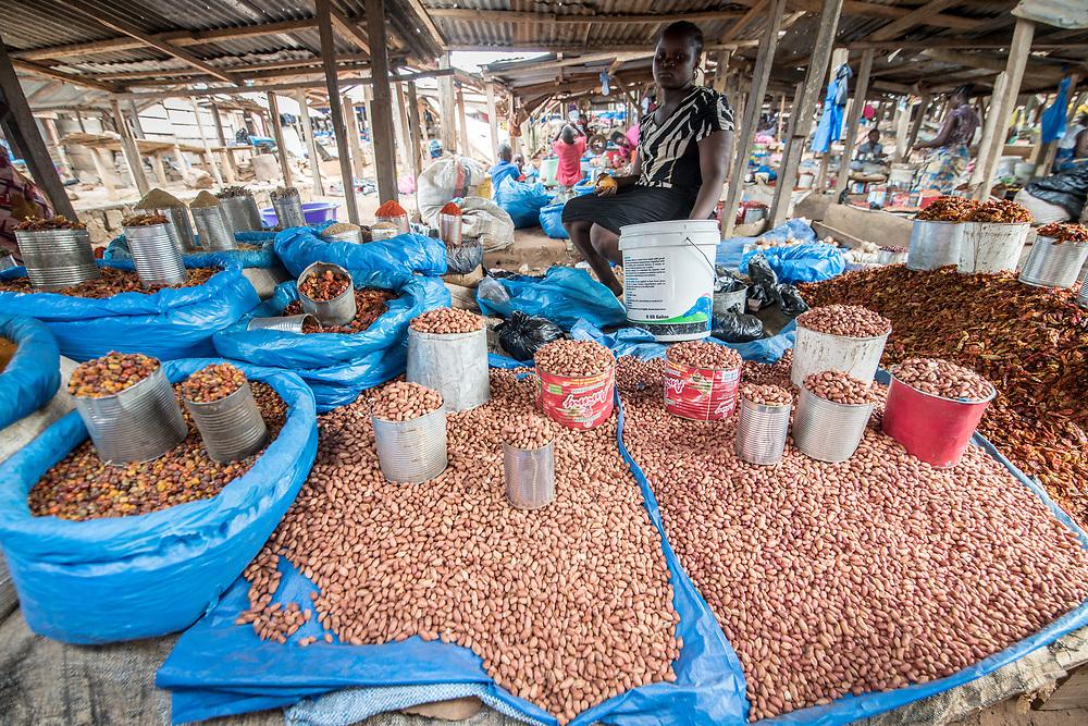 A woman sits amongst a pile of Palm kernels (Elaeis guineensis) in Ganta, Liberia