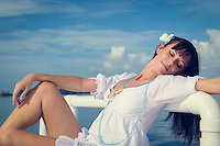 Young woman relaxing in a white dress with the ocean behind