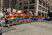"New York, NY - 25 June 2017. New York City Heritage of Pride March filled Fifth Avenue for hours with groups from the LGBT community and it's supporters. A group of marchers from Refuse Fascism with a street-wide banner reading ""Don't buy Trump's lies."""