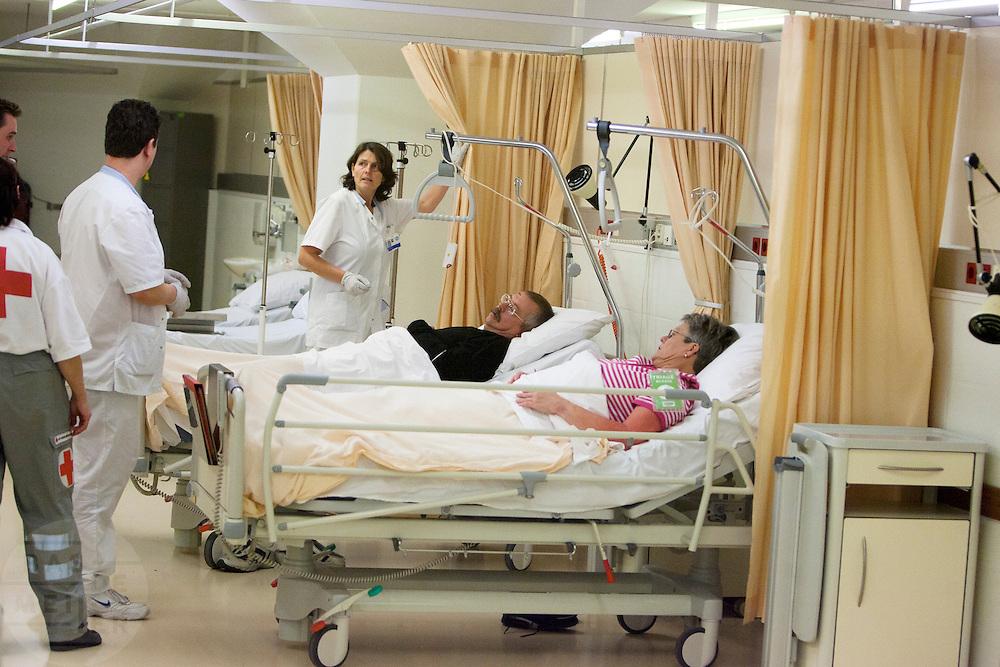 Slachtoffers op de verpleegafdeling. In het Calamiteitenhospitaal in Utrecht wordt een rampenoefening gehouden. De nadruk ligt op de contaminatie, door een gekantelde vrachtwagen zijn veel slachtoffers in aanraking gekomen met een chemische stof. Voor het eerst wordt er geoefend met een zogenaamde decontaminatietent. Als de tent bevalt, schaft het ziekenhuis zo'n tent aan. Bij de 'ramp' zijn 100 slachtoffers gevallen.<br /> <br /> Patients at the ward. In the Trauma and Emergency Hospital in Utrecht an calamity training was held. The emphasis is on the contamination by an overturned truck, many victims are contaminated by a chemical. For the first time a so-called decontamination tent was used. If the tent fulfills the expectations, a tent will be purchased. The 'calamity' caused 100 victims.