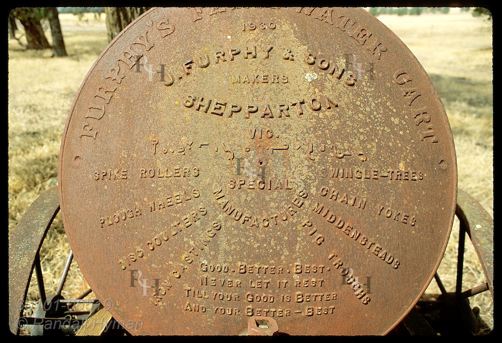 Rusty, old iron water tank advertises Australian farm implements from yesteryear; Coolamon, NSW Australia