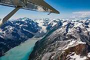 "Aerial view of Rendu Glacier & Rendu Inlet, in West Arm of Glacier Bay National Park, Alaska, USA. Flightseeing from Skagway or Haines is a spectacular way to see Glacier Bay. We were bedazzled by Mountain Flying Service's 1.3-hour West Arm tour from Skagway. Glacier Bay is honored by UNESCO as part of a huge Biosphere Reserve and World Heritage site shared between Canada and the United States. In 1750-80, Glacier Bay was totally covered by ice, which has since radically melted away. In 1794, Captain George Vancover found Icy Strait on the Gulf of Alaska choked with ice, and all but a 3-mile indentation of Glacier Bay was filled by a huge tongue of the Grand Pacific Glacier, 4000 feet deep and 20 miles wide. By 1879, naturalist John Muir reported that the ice had retreated 48 miles up the bay. In 1890, ""Glacier Bay"" was named by Captain Beardslee of the U.S. Navy. Over the last 200 years, melting glaciers have exposed 65 miles of ocean. As of 2019, glaciers cover only 27% of the Park area. Since the mid 1900s, Alaska has warmed 3 degrees Fahrenheit and its winters have warmed nearly 6 degrees. Human-caused climate change induced by emissions of greenhouse gases continues to accelerate warming at an unprecedented rate. Climate change is having disproportionate effects in the Arctic, which is heating up twice as fast as the rest of Earth."
