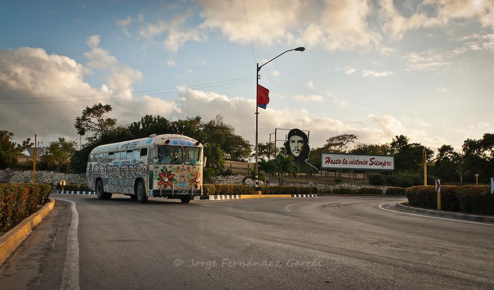 Painted bus driving on a road near Las Tunas near a Che propaganda bill. Las tunas, Cuba, Caribbean.