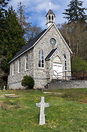 The historic St. Paul's Church at Fulford Harbour at Fulford Harbour on Salt Spring Island, British Columbia, Canada.  The church was founded in 1878 and built between 1880 and 1885.  The cross in the foreground is part of the church cemetery and marks the resting place of Alan Blackburn (1865-1925).