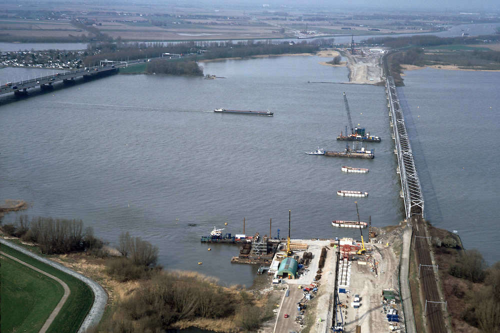 Nederland, Hollandsch Diep, 08-03-2002;in ZZO richting met Moerdijkbruggen, links van de vakwerk spoorbrug de Nieuwe Merwede, rechts de brug voor het wegverkeer (A16); HSL komt rechts van  bestaande spoorbrug te lopen, zand voor spoordijk reeds aanwezig (linksonder), bouw pijlers in het water; infrastructuur verkeer en vervoer spoor mobiliteit transport rivier binnenvaart landschap.<br /> luchtfoto (toeslag), aerial photo (additional fee)<br /> photo/foto Siebe Swart