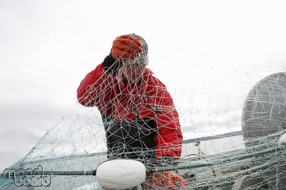 Fisherman holding fishing net on boat