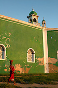 Ilha De Mocambique, Mozambique, Southern East Africa..Traditionally dressed woman walks past the only Mosque on the island of Ilha de Mocambique...© Demelza Cloke.DVD0001