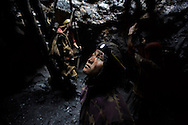 Meghalaya, India - April 29, 2014<br /> A young migrant coal miner from Nepal looks up from a mine hole in Jaintia Hills, Meghalaya in India on April 29, 2014. Indian government announced in September that it would double the coal production to one billion tons over the next four years to ease the ongoing power shortages. (Photo by Kuni Takahashi)