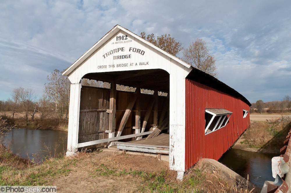 "Thorpe Ford Covered Bridge (163 feet long) was built in Burr Arch style over Big Raccoon Creek in 1912 by J.A. Britton on Catlin Road in Parke County, Indiana, USA. Red and white paint protects the wood. The traditional ""Cross this bridge at a walk"" sign required slow vehicle speed, but traffic is now diverted to an adjacent modern bridge."