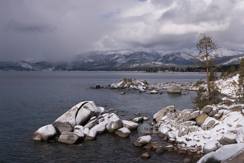 A photo of storm clouds and the shore of Lake Tahoe, NV covered in snow.