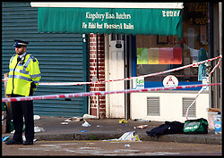 A police officer stands on duty near police clothing, and a medics bag on the pavement outside a Halal Butchers in Kingsbury where a man on the rampage attacked 4 police officers, stabbing 3 of them, Saturday Nov. 19, 2011.Photo by Morn/ i-Images