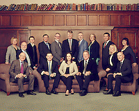 Large formal group shot taken in antiquated library setting with wood panels featuring team of management consultants