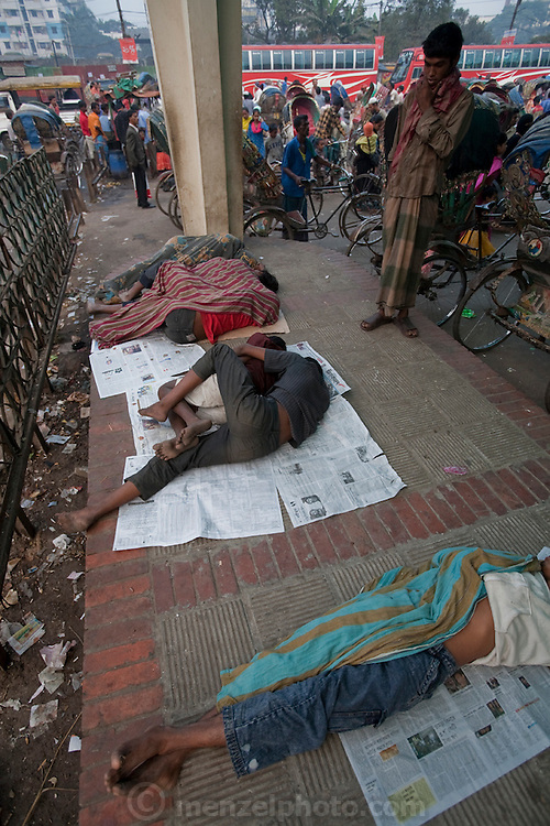 Young boys and men sleep on a pavement outside the Central Train Station in Dhaka, Bangladesh.