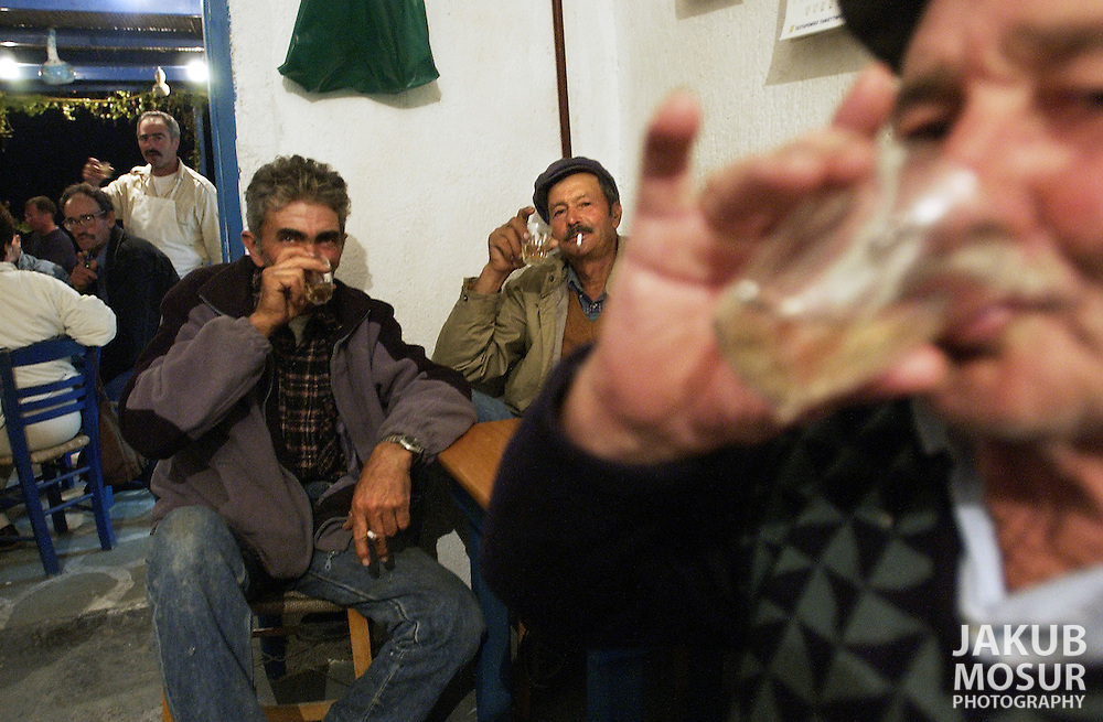 Greek patrons drink shots of wine at the Steki Tavern on the island of Anafi, Greece on October 19, 2002. Photo by Jakub Mosur