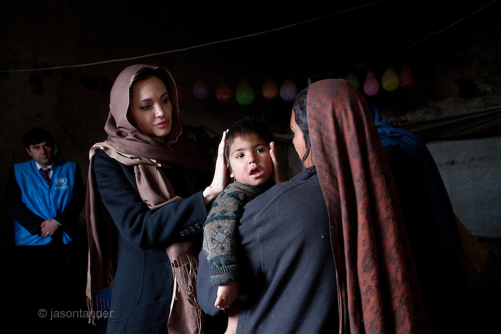 Afghanistan: UNHCR Goodwill Ambassador, Angelina Jolie, meets with  35 year old Khanum Gul, a mother of 8 and her youngest son, Samir at their makeshift home at Tamil Mill Bus site in Kabul city. ..When Angelina last visited Khanum Gul, Samir was a newly born baby of 14 days and he's two and a half years old, but having medical problems...Tajik and Pashtun families live side by side without any major conflict at the Tamil Mill Bus site. Over 70% of the families are returnees from the period 2002-2004 who are unable to achieve sustainable reintegration in their places of origin and subsequently drifted to Kabul City in search of work...There is a nearby school which is accessible to the children but the poor economic circumstances of the many families oblige them to send their children out to work. low levels of literacy, particularly amongst the women, limit their access to employment other than the lowest paid daily wage labour...Afghanistan/UNHCR/Jason Tanner/February 2011