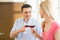 Couple toasting red wine glasses in kitchen