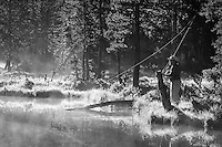 A fly fisherman prepares to cast on a calm backcountry lake early in the morning as the mist rises. Monochrome version.