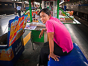 11 JULY 2011 - BANGKOK, THAILAND:    A snack vendor on a platform in Hua Lamphong train station in Bangkok. Hua Lamphong Grand Central Railway Station, officially known as the Bangkok Grand Central Terminal Railway Station, is the main railway station in Bangkok, Thailand. It is located in the center of the city in Pathum Wan District, and is operated by the State Railway of Thailand. The station was opened on 25 June 1916, after six years' construction. The station was built in an Italian Neo-Renaissance style, with decorated wooden roofs and stained glass windows. The architecture is attributed to Turin-born Mario Tamagno, who, with countryman Annibale Rigotti made a mark on early 20th century public building in Bangkok. The pair also designed Bang Khun Prom Palace (1906), Ananda Samakhom Throne Hall in The Royal Plaza (1907-15) and Suan Kularb Residential Hall and Throne Hall in Dusit Garden, among other buildings..There are 14 platforms and 26 ticket booths. Hua Lamphong serves over 130 trains and approximately 60,000 passengers each day. Thailand has the most advanced rail system in Southeast Asia and trains from Hua Lamphong serve all corners of the Kingdom.      PHOTO BY JACK KURTZ