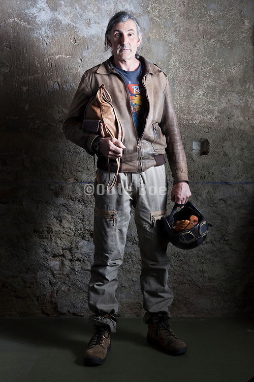 portrait if man holding a motorcycle helmet