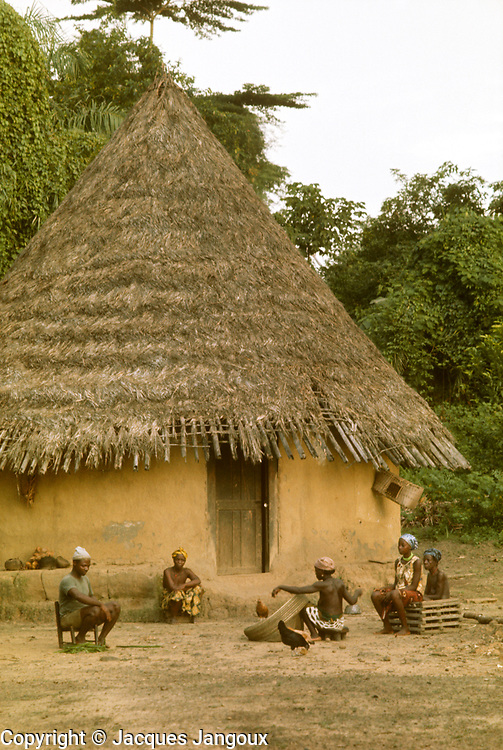 Village life in Africa: Africa, Liberia, Kpelle (Guerze) tribe: village scene: traditional cylindrical hut with conical thatch roof. Woman is making a fishing net.