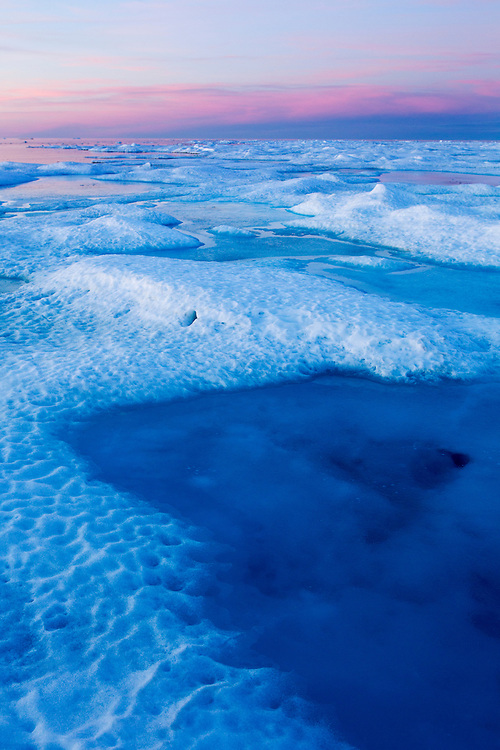 Canada, Manitoba, Churchill, Midnight sun lights cirrus clouds above melting ice on Hudson Bay