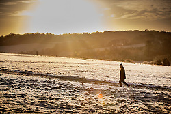 © Licensed to London News Pictures. 03/01/2017. Epsom, UK. A man walks on a frost covered Epsom Downs. Parts of the UK are experiencing temperatures as low as -5 degrees centigrade. Photo credit: Peter Macdiarmid/LNP
