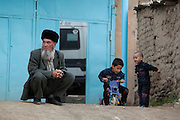 Turkmen man sitting on his haunches outside a house in Nohur village, Kopet Dag mountains
