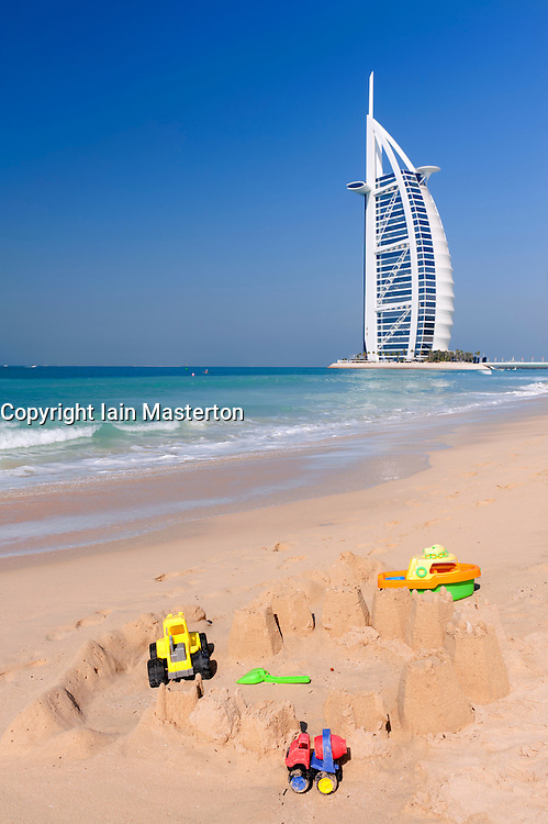 View of Burj al Arab hotel with childrens' toys and sandcastles  in foreground  in Dubai in United Arab Emirates