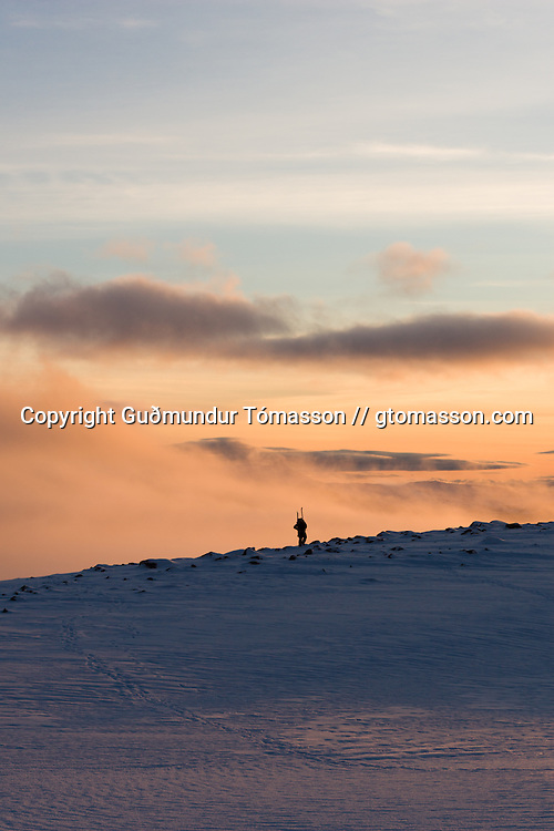 A man walking with skis on his backpack, Tindfjöll, Iceland.