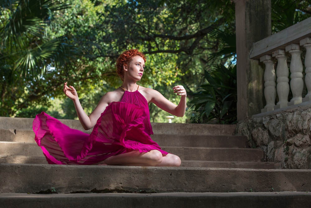 Young woman in hot pink dress sitting on stone steps looking like Greek Goddess.