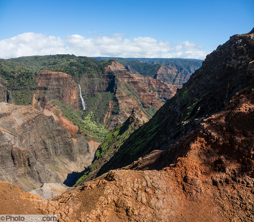 """Seen from Waimea Canyon Drive, Waipoo Falls plunges in a cascade for 800 feet in Waimea Canyon State Park on the island of Kauai, Hawaii, USA. Waimea Canyon (""""the Grand Canyon of the Pacific"""") slices as much as 3000 feet deep across ten miles of western Kauai. About 4 million years ago, a catastrophic collapse of the volcano that created Kauai created a fault which was gradually cut deeper by the Waimea River, fed by extreme rainfall on the island's central peak, Mount Wai'ale'ale, among the wettest places on Earth. Waimea is Hawaiian for """"reddish water,"""" referring to the local orange clay. This image was stitched from multiple overlapping images."""