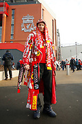 Liverpool fan draped in flags and badges during the Premier League match between Liverpool and Manchester United at Anfield, Liverpool, England on 19 January 2020.