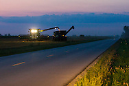 Headlights of passing cars light the pavement of the county highway as a combine unloads a crop of summer wheat into a waiting wagon.