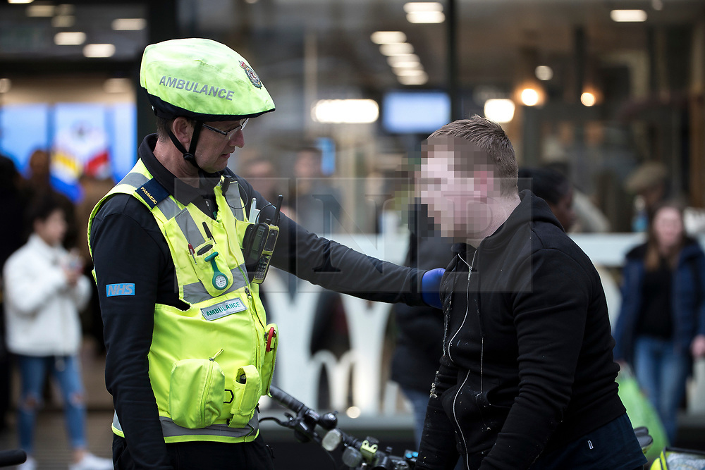 © Licensed to London News Pictures . 06/04/2017 . Manchester , UK . A paramedic tends to a man , believed to have consumed spice , in Piccadilly Gardens . An epidemic of abuse of the drug spice by some of Manchester's homeless population , in plain sight , is causing users to experience psychosis and a zombie-like state and is daily being witnessed in the Piccadilly Gardens area of Manchester , drawing large resource from paramedic services in the city centre . Photo credit : Joel Goodman/LNP