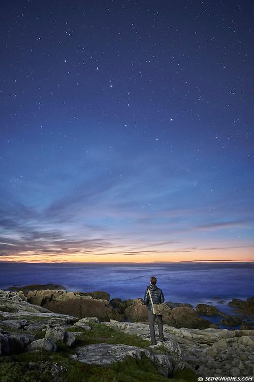 A man stargazing on Fogo Island, Newfoundland, Canada.