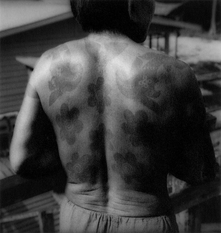 Tattooed Iban Dayak man outside Rumah Enggin Longhouse, Sarawak, Malaysian Borneo.