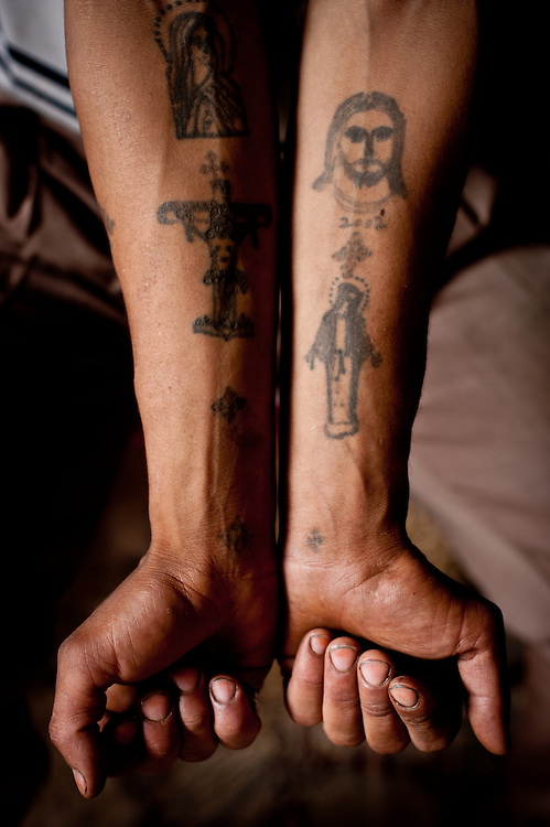 A coffee shop worker shows his Christian tattoos.