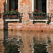 Reflections of brick wall, windows, and window boxes with red geraniums in the water of the canal Rio de Orseolo, Venice, Italy<br />