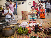 "07 AUGUST 2014 - BANGKOK, THAILAND: People pray in front of food left for the poor at Pek Leng Keng Mangkorn Khiew Shrine. Thousands of people lined up for food distribution at the Pek Leng Keng Mangkorn Khiew Shrine in the Khlong Toei section of Bangkok Thursday. Khlong Toei is one of the poorest sections of Bangkok. The seventh month of the Chinese Lunar calendar is called ""Ghost Month"" during which ghosts and spirits, including those of the deceased ancestors, come out from the lower realm. It is common for Chinese people to make merit during the month by burning ""hell money"" and presenting food to the ghosts. At Chinese temples in Thailand, it is also customary to give food to the poorer people in the community.     PHOTO BY JACK KURTZ"