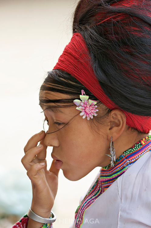 Red Hmong woman wearing hair interwoven with red wool.